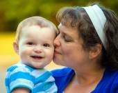 Happy baby kissed by mom — Stock Photo