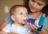 Infant getting breathing treatment from mother while suffering f — Stock Photo