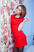 Woman in red dress sitting on a bed — Stock Photo
