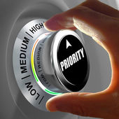 Hand rotating a button and selecting the level of priority. — Stock Photo