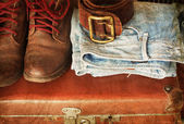 Pair of jeans, shoes, belt in a vintage suitcase — Stock Photo