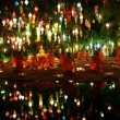 Thai monks meditate around buddha statue among many lanterns — Stock Photo #57889253