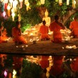 Thai monks meditate around buddha statue among many lanterns — Stock Photo #57889259
