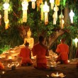 Thai monks meditate around buddha statue among many lanterns — Stock Photo #57889909