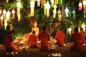 Thai monks meditate around buddha statue among many lanterns  — Stock Photo