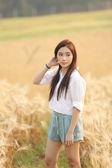 Asian girl on wheat field — Stock Photo