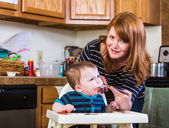 Woman Feeds Baby in Kitchen — Stock Photo