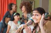 Cringing Woman and Singing Friends — Stockfoto