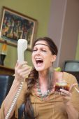 Woman singing into telephone — Stock Photo