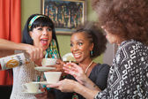 Excited women drinking booze in teacups — Stock Photo
