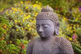 Grinning Stone Buddha statue — Stock Photo