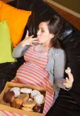 Donut Eating Pregnant Woman on Sofa — Stock Photo