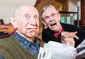 Old mad couple reading newspaper — Stock Photo