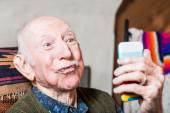 Older man taking silly face selfie — Stock Photo