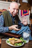 Elderly man with sandwich — Stock Photo