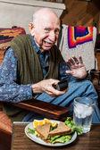 Grumpy elderly man with sandwich — Stock Photo