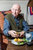 Elderly man holding sandwich — Stock Photo