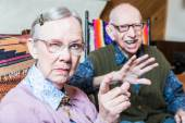 Couple in living room woman pointing — Stock Photo