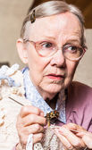 Old woman crocheting with worried expression — Stock Photo