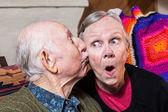 Elderly gentleman kissing elderly woman — Stock Photo