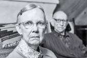 Elderly scowling couple seated — Stock Photo