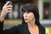 Woman taking selfie with black cellphone — Stock Photo