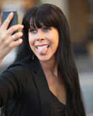 Woman sticks out tongue taking selfie — Stock Photo