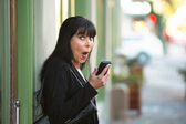 Woman with cellphone on downtown street — Stock Photo