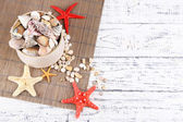 White box full of sea gifts on white wooden background — Stock Photo