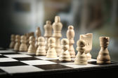 Chess board with chess pieces on dark background — Stock Photo