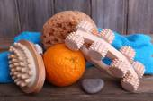 Roller brush, mop, towel, orange and oval brushes on wooden table in front of wooden wall — Стоковое фото