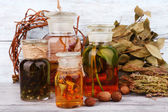 Bottles of herbal tincture and dried leaves on wooden background — Stock Photo