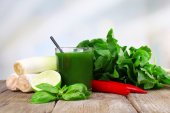 Fresh vegetable juice with spring onion, tuft of sorrel and chilly pepper on wooden table — Stock Photo