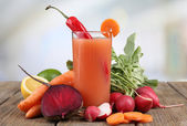 Fresh carrot juice with vegetables on wooden table — Stockfoto