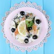 Fresh prawns with olives, lemon and parsley in white sauce on pink round plate on a lace napkin on blue wooden background — Stock Photo #51900831