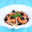 Fresh prawns with spaghetti, olives and parsley in tomato sauce in a round white plate on blue wooden background — Stock Photo #51900849