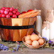 Big round basket with dried grass, vegetables, milk and fresh eggs on sacking background — Stock Photo #51901941