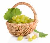 Sweet grapes in wicker basket isolated on white — Stock Photo