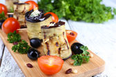 Fried aubergine with cottage cheese and parsley in n a cutting board on a napkin — Stock Photo