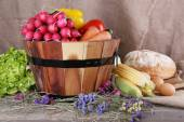 Big round wooden basket with vegetables, milk and bread on sacking background — Foto de Stock