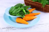 Carrots and sorrel on blue round plate on wooden background — Stockfoto