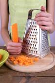 Woman grating carrot in kitchen on light background — Stock Photo
