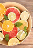 Different sliced juicy citrus fruits in bowl on wooden table — Stock Photo