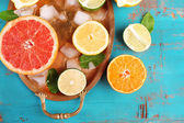Different sliced juicy citrus fruits with ice on tray, on blue wooden table — Stok fotoğraf