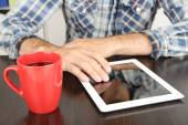 Man sitting on wooden table and working on tablet closeup — Stock Photo