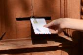 Letter in hand near postbox — Stock Photo