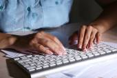 Female hands typing on keyboard, close-up, on dark background — Stock Photo