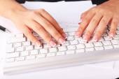 Female hands typing on keyboard, close-up, on light background — Stock Photo
