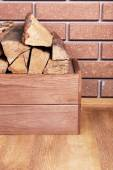 Wooden box of firewood on floor on brick background — Stockfoto
