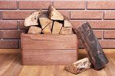 Wooden box of firewood on floor on brick background — Stock Photo